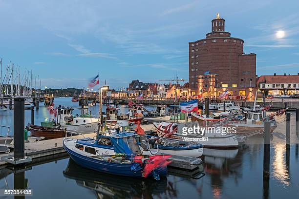Germany, Eckernfoerde, fishing boats in harbor and silo at full moon