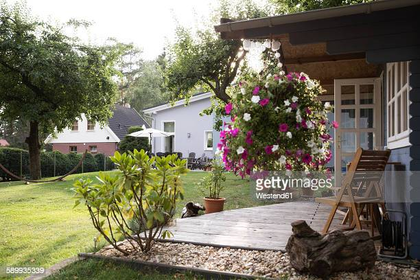 Germany, Eggersdorf, house with garden and flowers at terrace