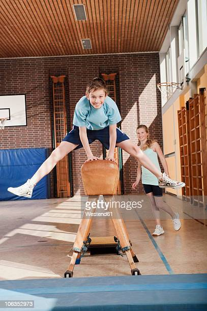 Germany, Emmering, Boy (12-13)  jumping with girl standing in background