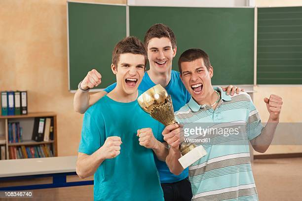Germany, Emmering, Friends holding trophy and clenching fist, smiling