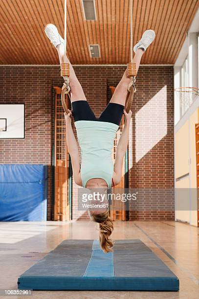 germany, emmering, girl hanging from flying rings, smiling, portrait - school gymnastics stock photos and pictures