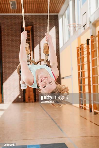 Germany, Emmering, Girl (12-13) hanging from flying rings, smiling, portrait