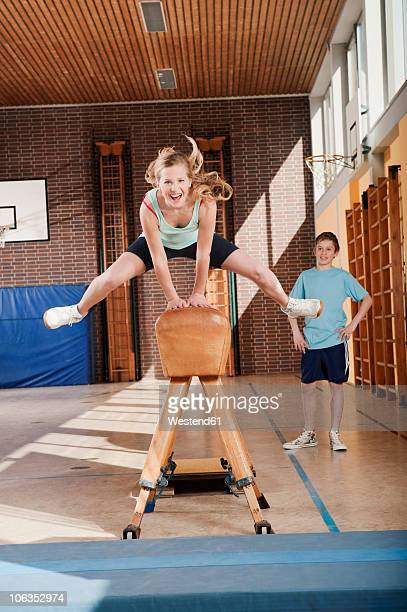 Germany, Emmering, Girl (12-13) jumping with boy standing in background
