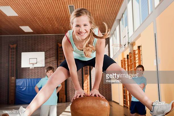 germany, emmering, girl jumping with boys standing in background - physical education stock photos and pictures