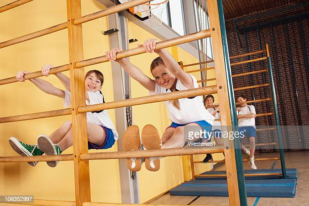 Germany, Emmering, Girls (12-14) climbing wall bars with boys in background