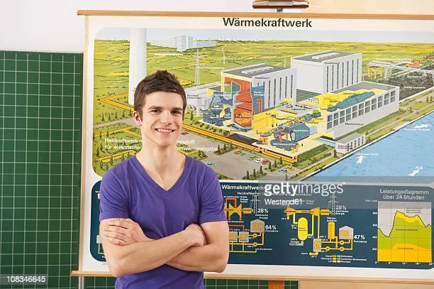 Germany, Emmering, Teenage boy arms crossed, smiling, portrait