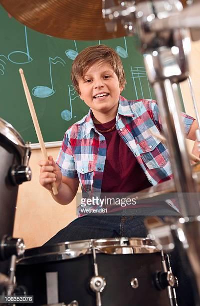 Germany, Emmering, Teenage boy (14-15) playing drumset, portrait, smiling