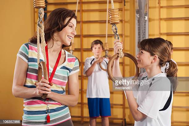 germany, emmering, woman and girl holding gymnastic rings with boy in background - pe teacher stock photos and pictures