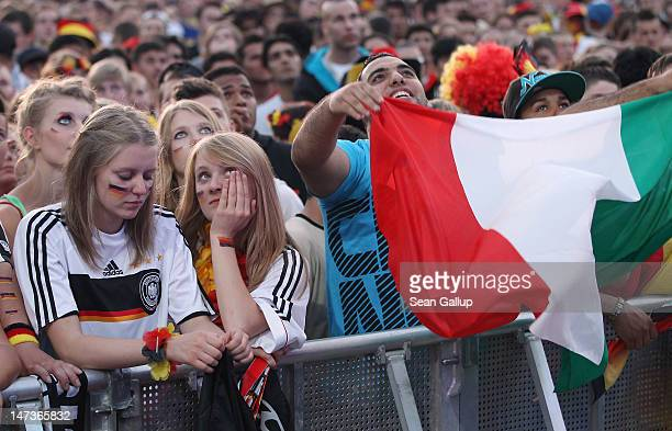 Germany fans and one Italian fan react to the second Italian goal against Germany at the Fanmeile public viewing at Brandenburg Gate during the...
