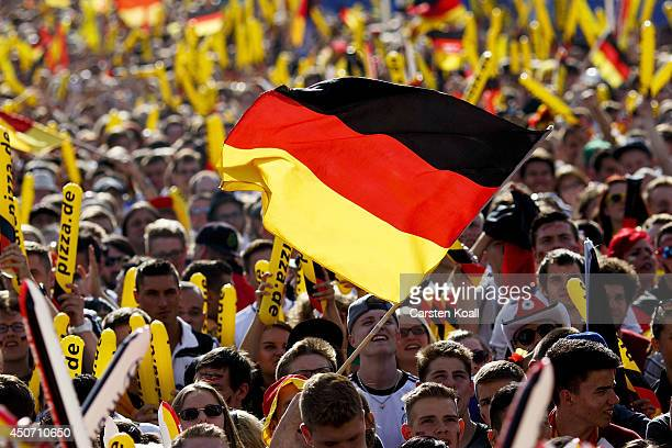 Germany fans celebrate during a public viewing at Strasse des 17 Juni close to the Brandenburger Tor watching the 2014 FIFA World Cup match between...