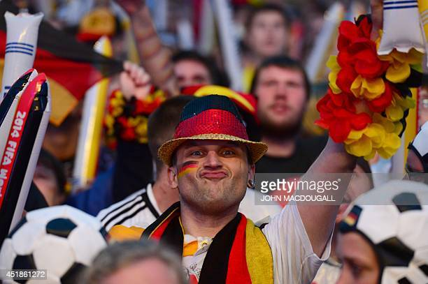 A Germany fans cheers prior to the FIFA World Cup 2014 semi final football match between Germany and Brazil during public viewing at the Brandenburg...
