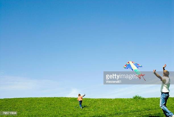Germany, father and son (6-7) flying kite in meadow
