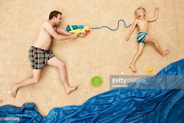 Germany, Father and son playing with water guns at beach