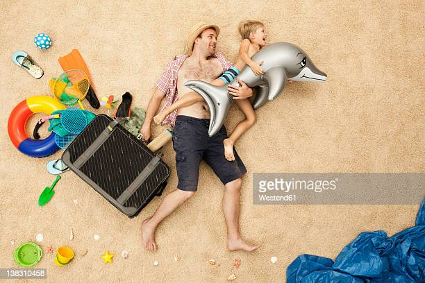 Germany, Father and son with toys and baggage at beach