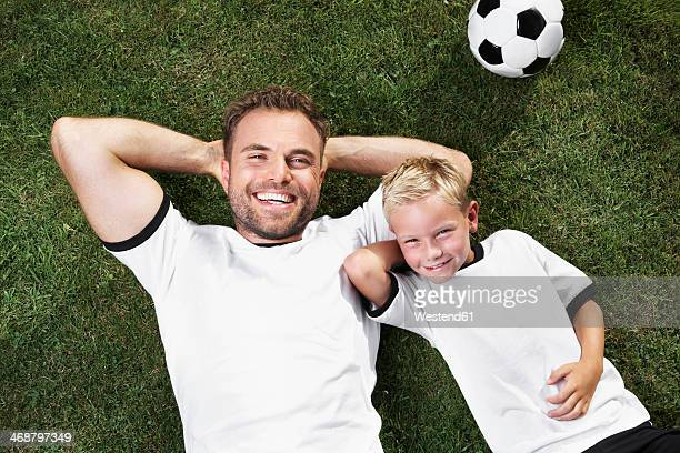 germany, father and sun lying on lawn, wearing football shirts - fußballtrikot stock-fotos und bilder