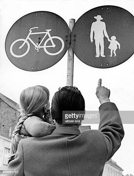 Father explaining traffic signs to his daughter In the sixties