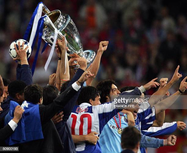 FC Porto players celebrate while holding the trophy after beating Monaco 30 in the final of the Champions league football match 26 May 2004 at the...