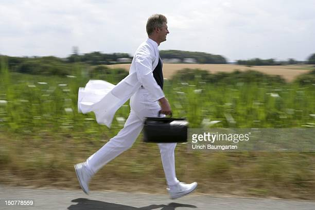 Germany Feature to the topic shortage of doctors in the country Our picture shows a country doctor runs along a field
