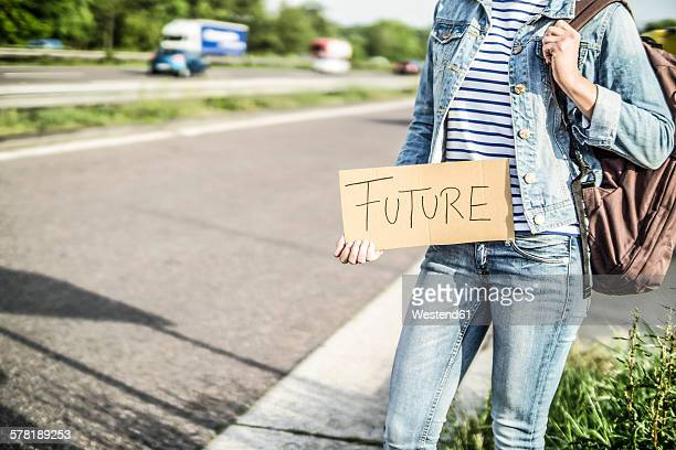 germany, female hitchhiker with sign 'future' waiting at roadside - hitchhiking stock pictures, royalty-free photos & images