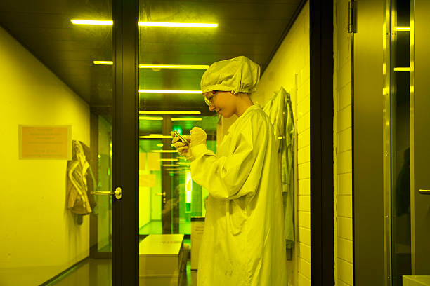 Germany, Female technician working in optical clean room unit, using mobile phone
