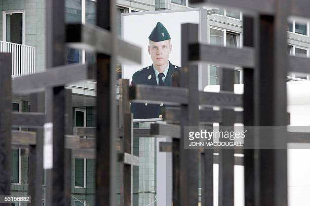 FILES A file picture taken on 07 November 2004 shows a portrait of a US soldier peering through some of the 1065 crosses at a memorial dedicated to...