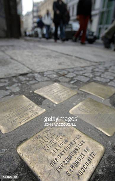 """File picture taken on 19 January 2005 shows people walking past a cluster of five """"Stolpersteine"""" or stumbling stones in Berlin's old Jewish quarter...."""