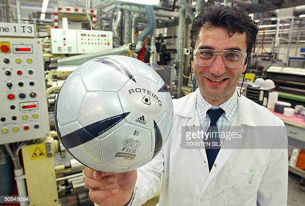 FILES An employee of German chemicals giants Bayer MaterialScience presents the new Euro 2004 football 'Roteiro' 04 June 2004 at the Bayer plant in...