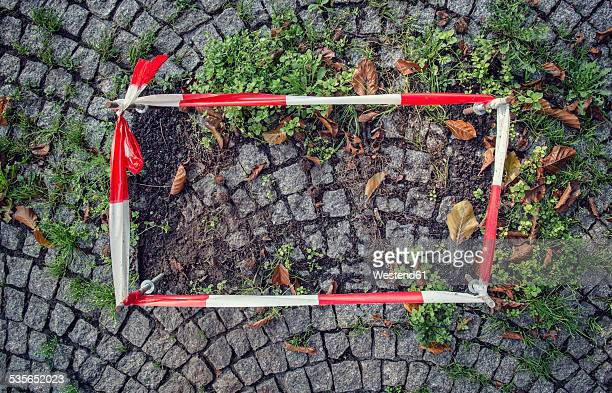 Germany, fixed barrier tape arround damaged cobblestone pavement
