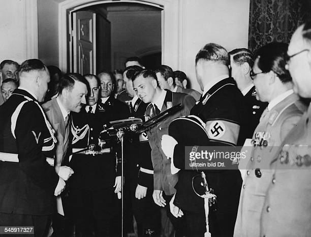 Germany Flight captain Hans Baur presenting Adolf Hitler on the occasion of Hitler's 50th birthday the model of the new Heinkel aircraft behind the...