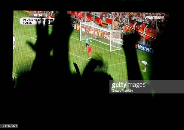 Germany football fans celebrate the goal as they watch the Germany v Poland match on the large screen in the Kur Park in Wiesbaden during the FIFA...