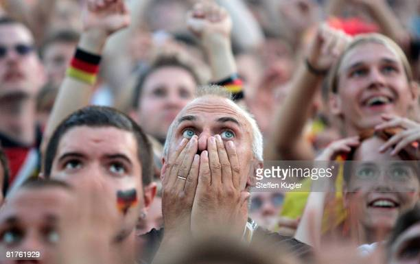 Germany football fans react while watching the UEFA EURO 2008 final match between Germany and Spain at the Fan Mile public viewing area in front of...