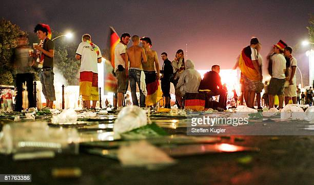 Germany football fans stand in the midst of rubbish after watching the UEFA EURO 2008 final match between Germany and Spain at the Fan Mile public...
