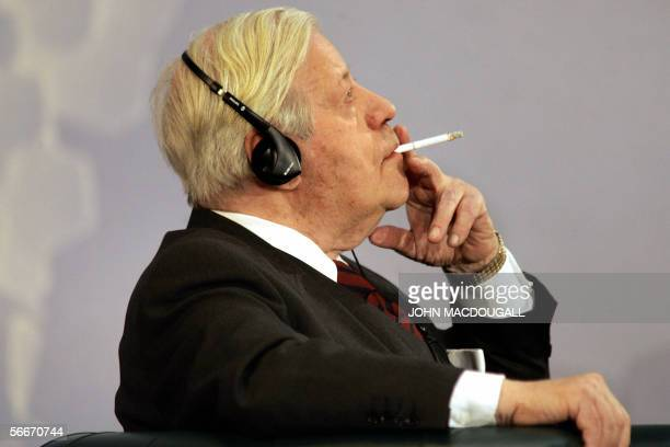 Former German chancellor Helmut Schmidt smokes a cigarette as he takes part in a debate with former French president Valery Giscard d'Estaing...