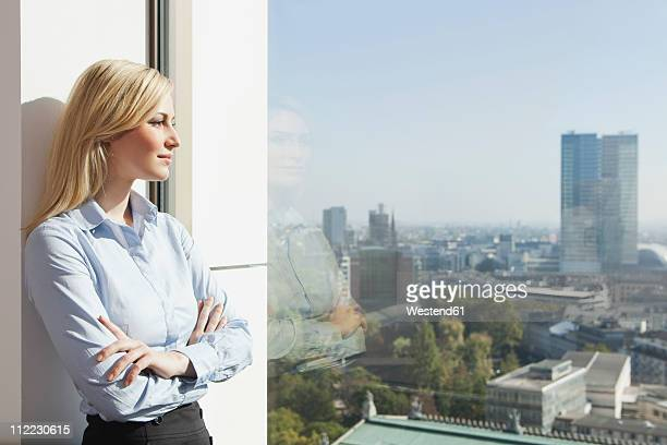 Germany, Frankfurt, Business woman looking through window
