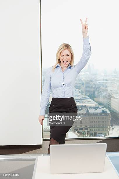 Germany, Frankfurt, Business woman showing v sign