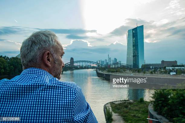 Germany, Frankfurt, businessman at river Main with European Central Bank Headquarters in background