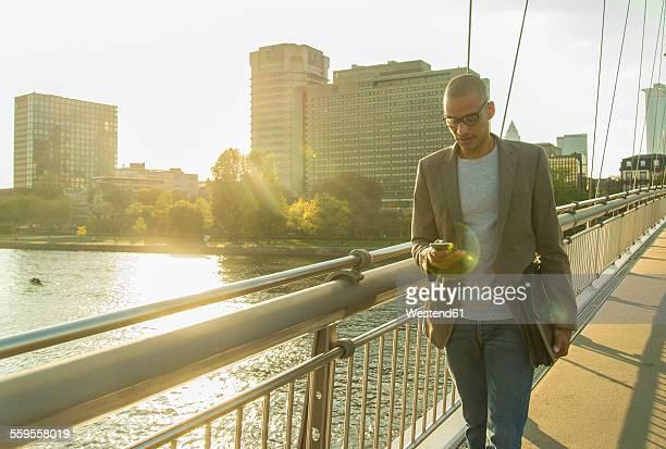 Germany, Frankfurt, businessman on bridge looking on smartphone