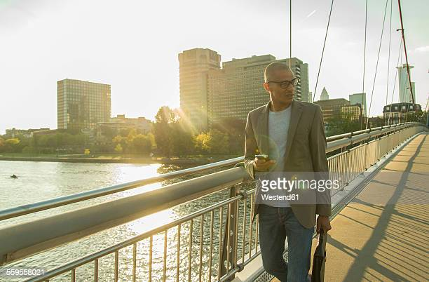 Germany, Frankfurt, businessman walking on bridge