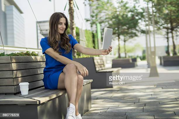 Germany, Frankfurt, businesswoman sitting on a bench taking a selfie with mini tablet