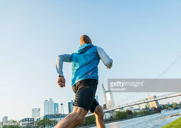 Germany, Frankfurt, man jogging by the riverside