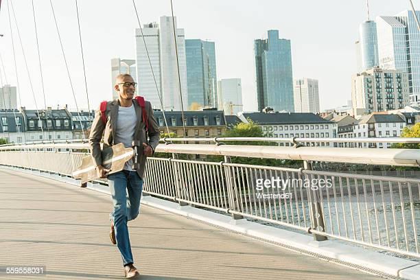 Germany, Frankfurt, man running with skateboard on bridge