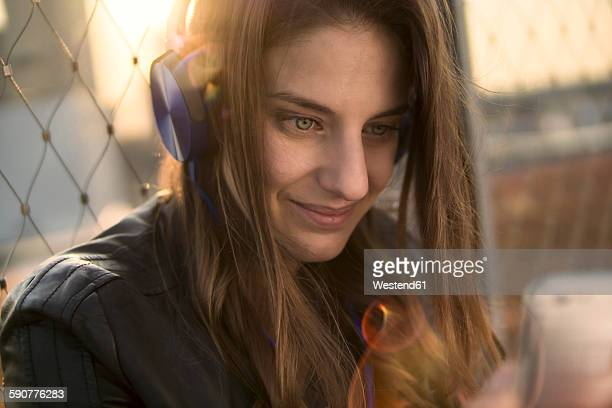Germany, Frankfurt, portrait of smiling woman hearing music with headphones looking at smartphone