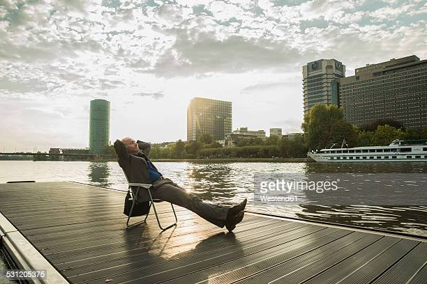 germany, frankfurt, relaxed businessman at river main - flussufer stock-fotos und bilder