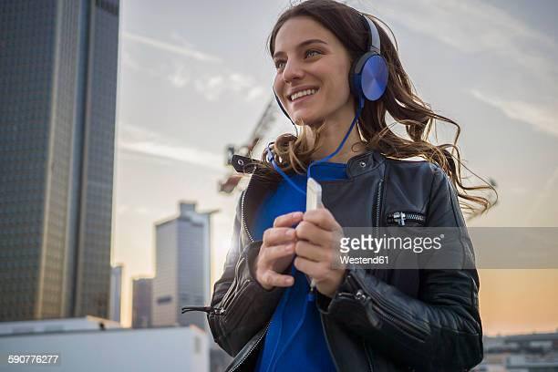 Germany, Frankfurt, smiling woman hearing music with headphones dancing