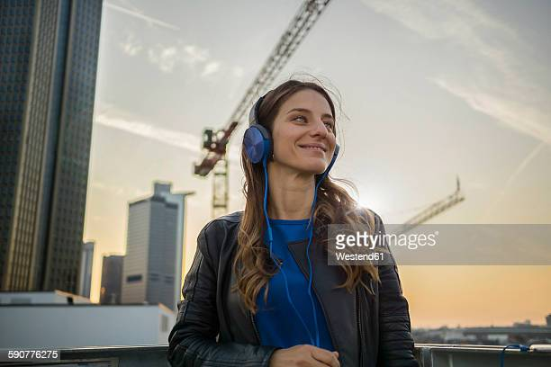 Germany, Frankfurt, smiling woman hearing music with headphones