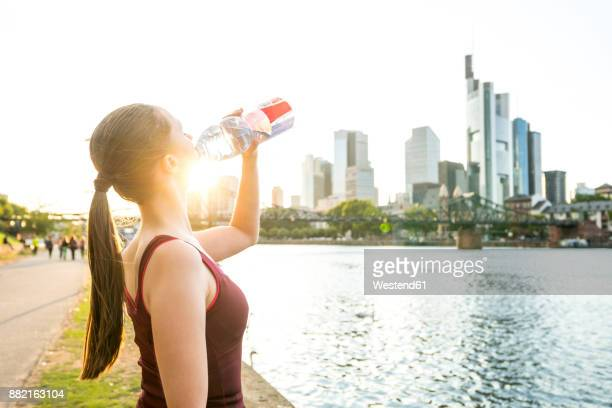 Germany, Frankfurt, sportive young woman drinking from bottle at riverside