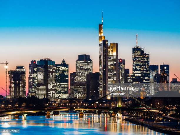 Germany, Frankfurt, view to skyline with Floesserbruecke and Main River in the foreground at twilight