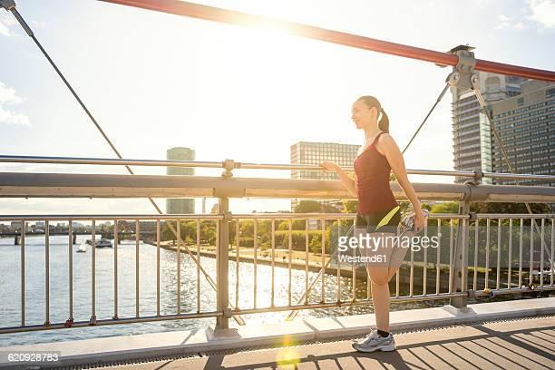 Germany, Frankfurt, young athlete stretching on bridge