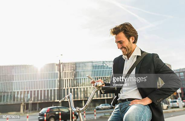 Germany, Frankfurt, Young businessman in the city with bicycle, using mobile phone
