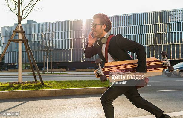 Germany, Frankfurt, Young businessman running with skateboard under his arm, using mobile phone